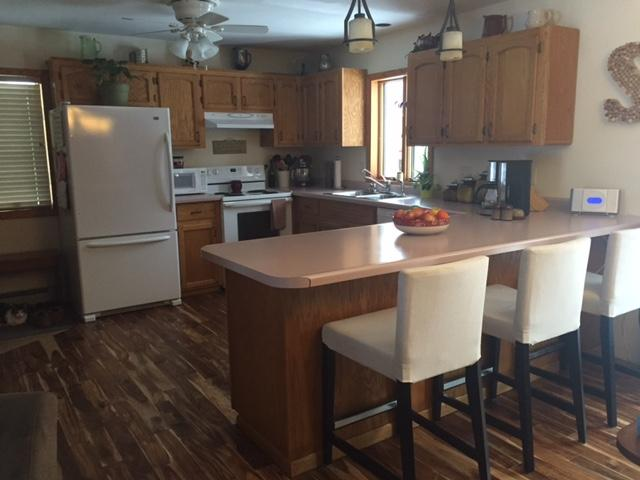 Spacious and very functional kitchen features a breakfast bar.