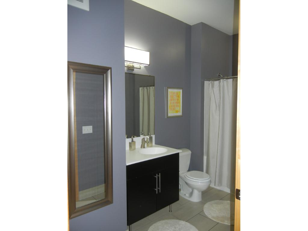 Large bathroom with bath tub, solid surface counter top and white subway tile shower surround
