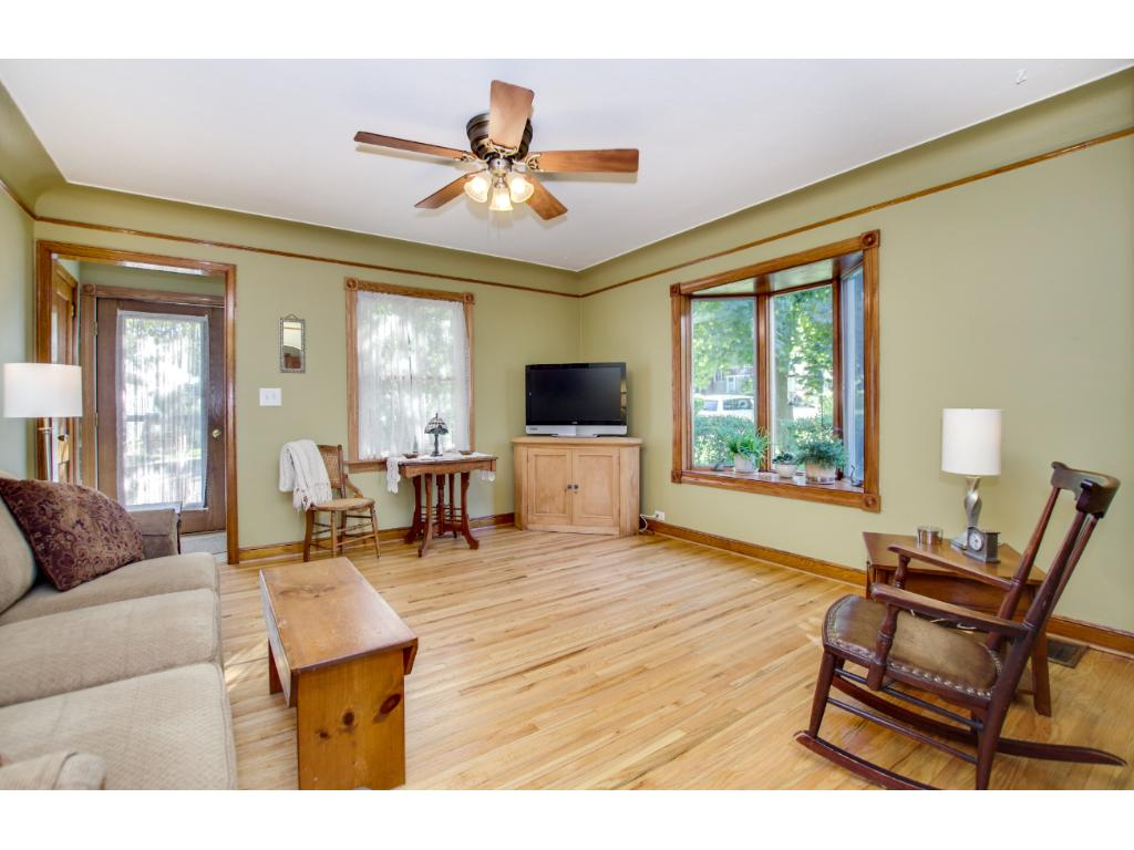 """The living room boasts a south facing """"bowed"""" window and original wood floors. Lots of natural light and a room big enough for the whole family"""