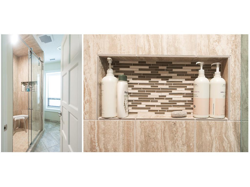 Master walk in stone and tiled shower with built in shelving accented by glass tile!
