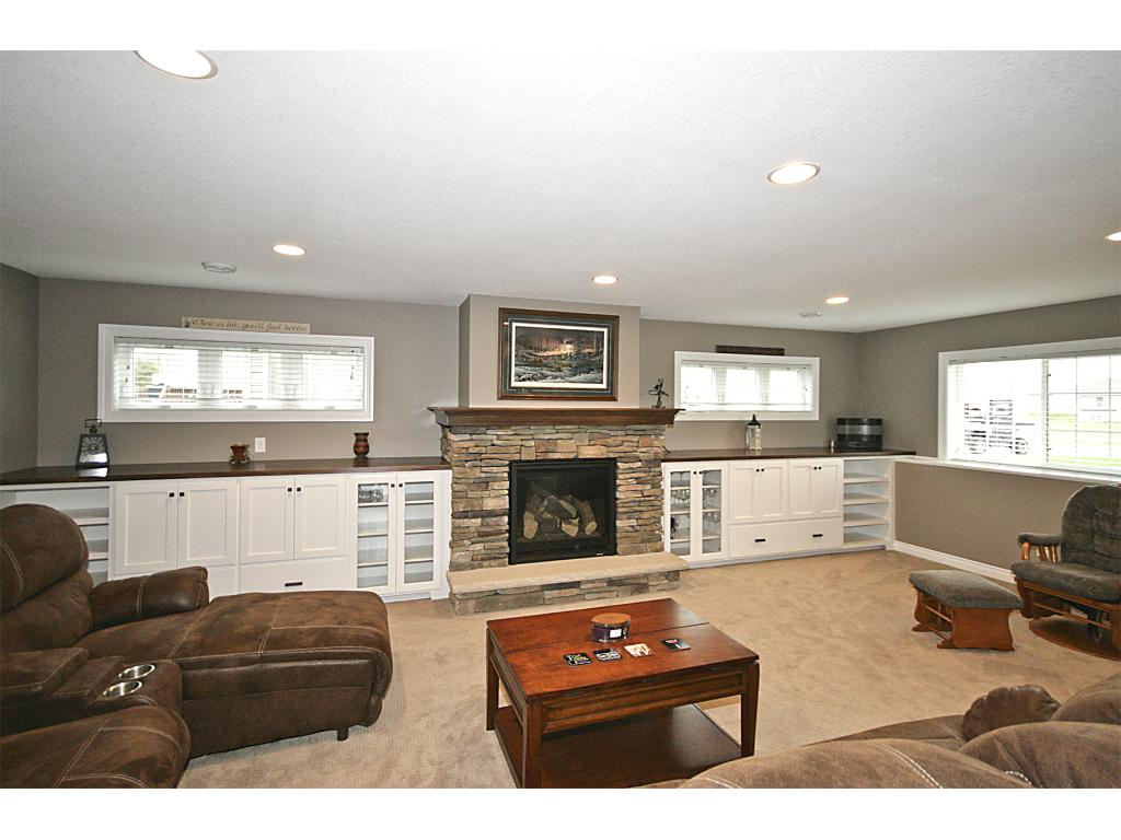 Your family will be spending a lot of time in this cozy family room! LL family room with white wood work throughout, built-ins, gas fire place, dry bar and recessed lighting.
