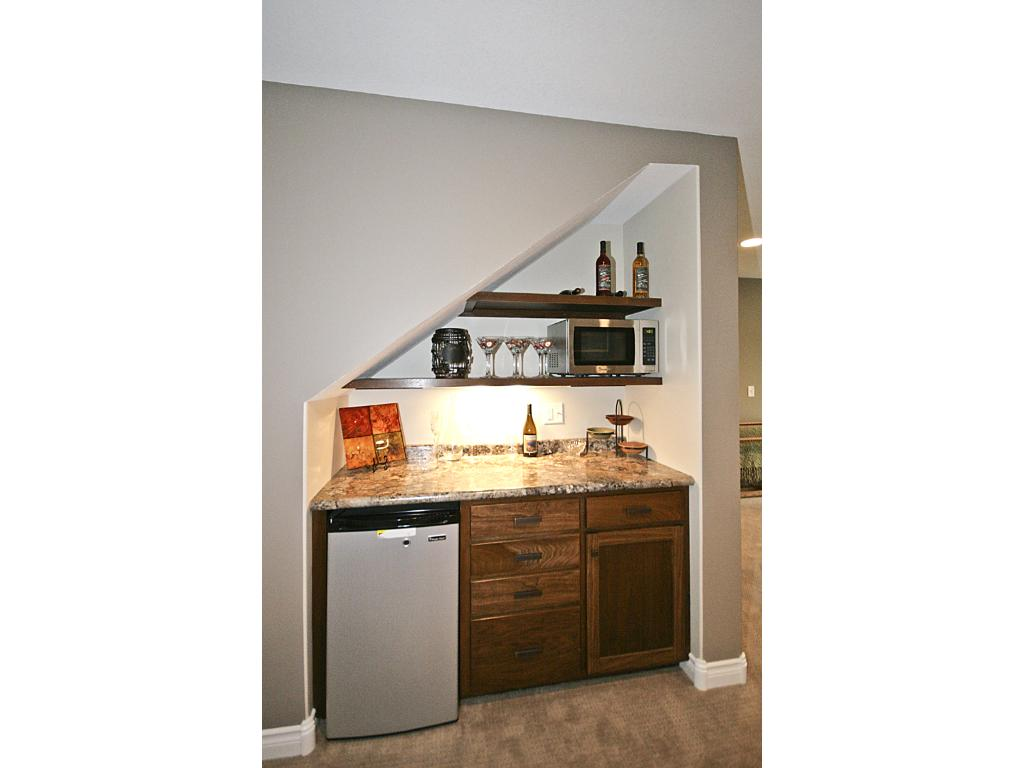 Built-in dry bar area in lower level family room with microwave and mini-fridge.