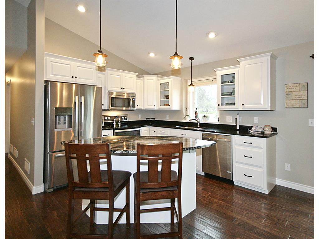 Granite counter tops and island, white cabinetry, SS appliances and pantry.