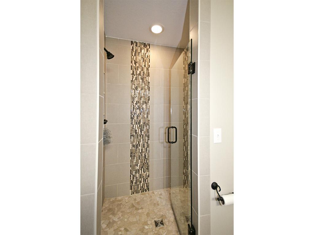 3/4 master bathroom with ceramic tile walk-in shower and glass swing door.