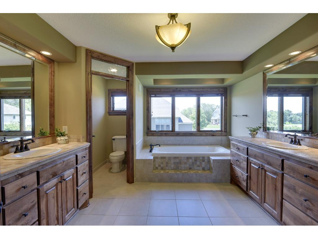 Owner's private bath with separate tub and walk-in shower, custom-built cabinet for linens, dual vanities, private bathroom, and stunning detail.