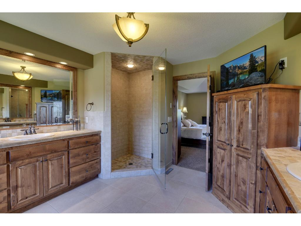 Walk-in shower with dual shower heads, large custom-built cabinet for linens and television connection above.