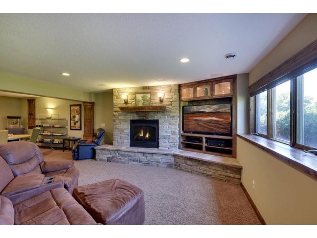Spacious family room in the lower level. Warm stone fireplace.