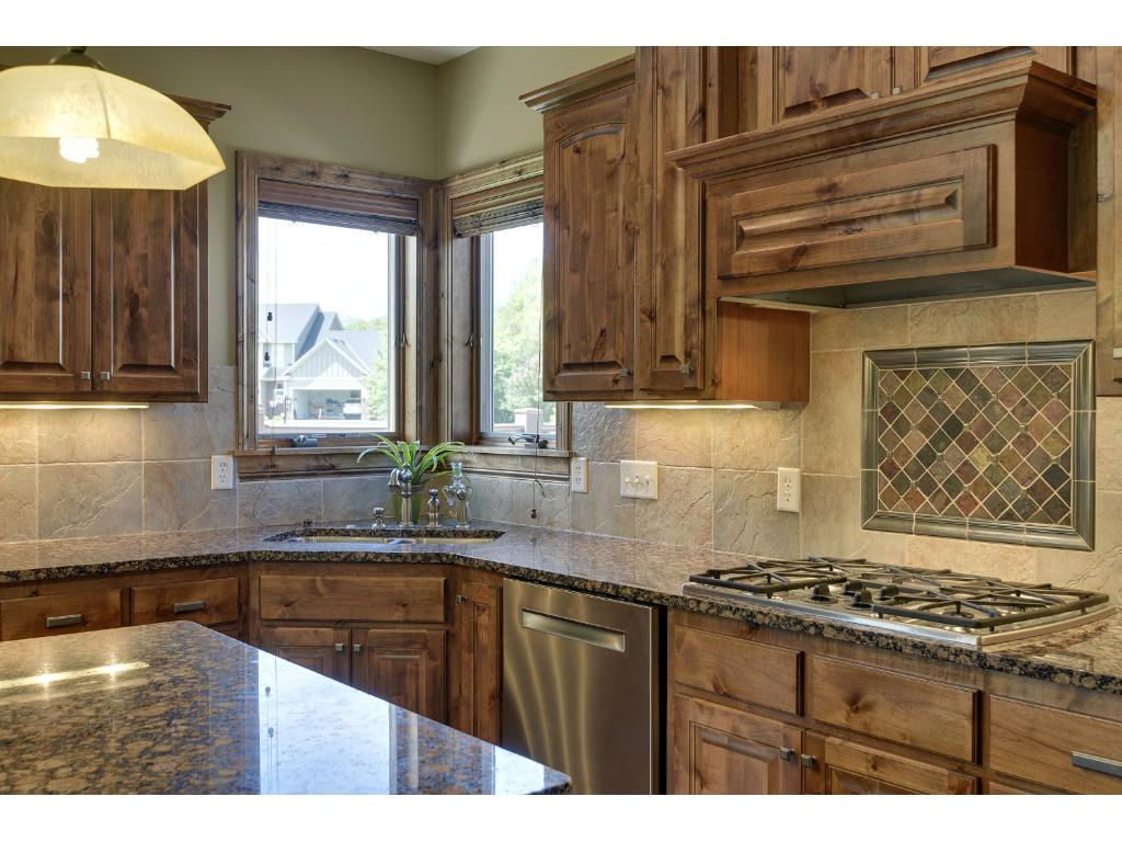 Granite counter tops, knotty alder cabinetry, and custom tile back splash add to the elegance of this luxurious kitchen.