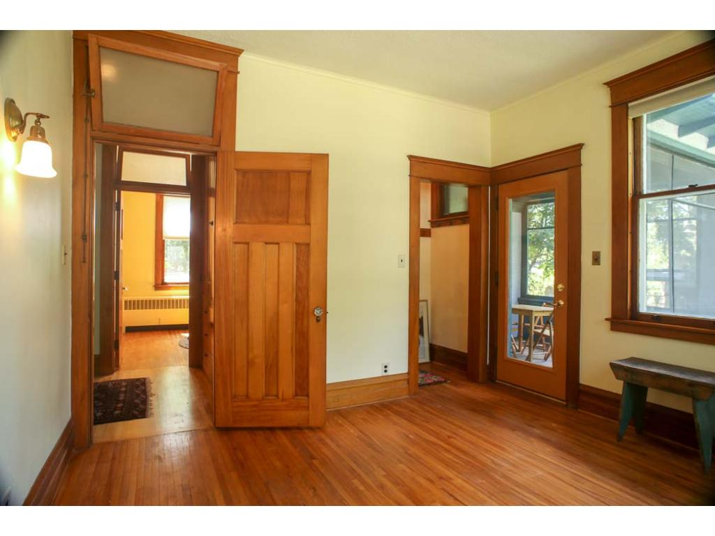 Here is a main floor bedroom with a door out to the screened in porch.  Notice the gleaming hardwood floors and doors.