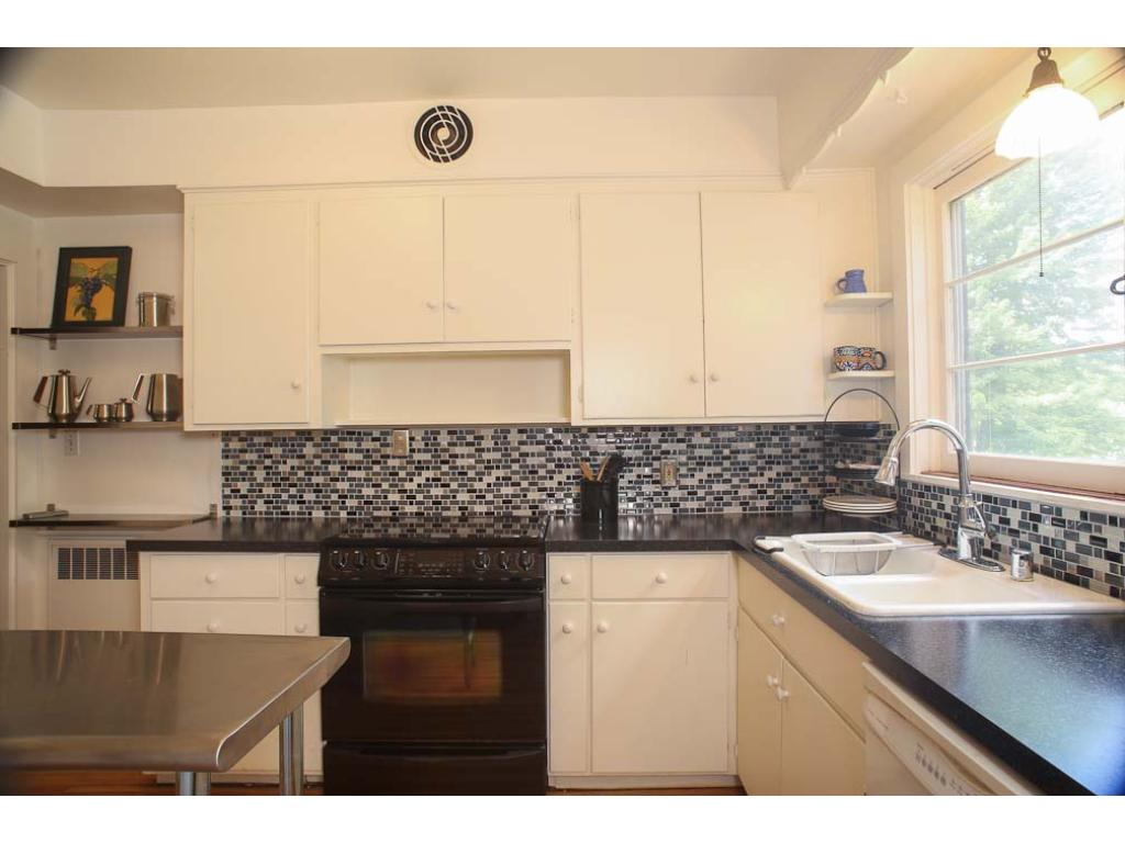 Another view of the kitchen with tile backsplash and large windows making the space bright.