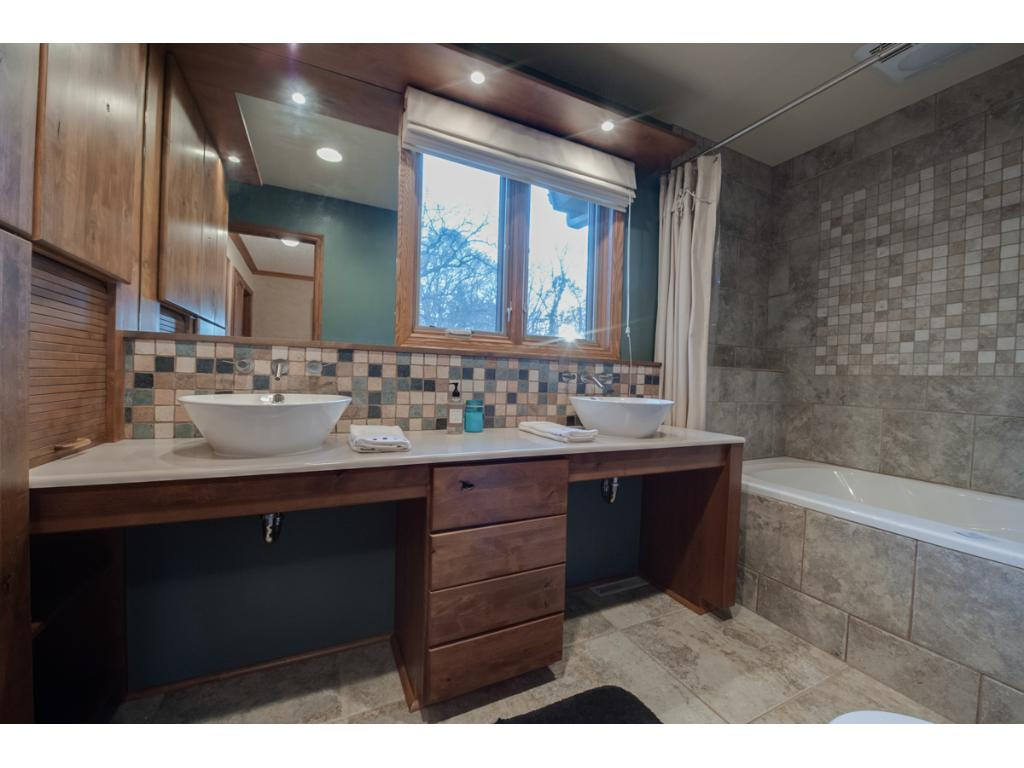 Main bath on upper level has two sinks, loads of storage and a beautiful tile shower surround.