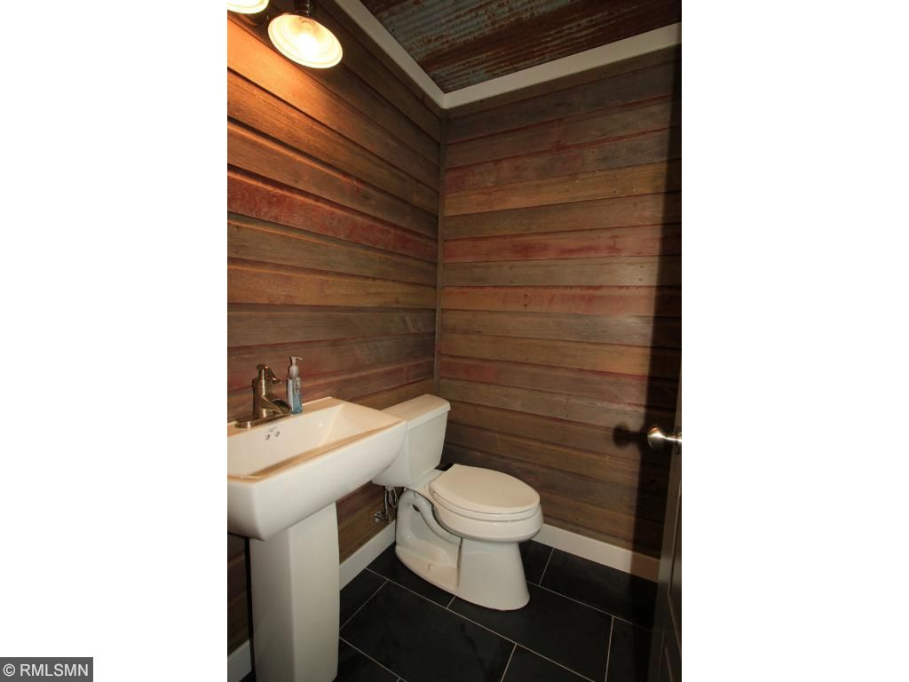 Main floor powder room features reclaimed barn wood on the walls as well as reclaimed tin ceiling.