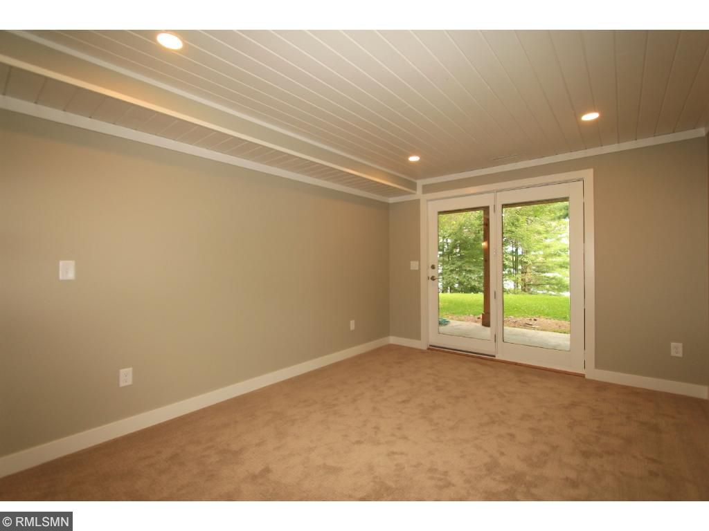 Walkout lower level bedroom is lakeside offering stunning lake views and access to the lakeside patio.