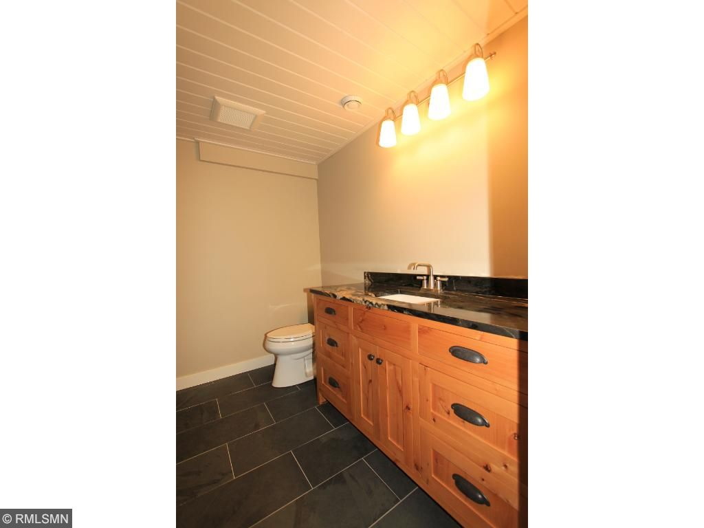 Lower level three fourths bathroom offers a Knotty alder vanity and custom tile work.