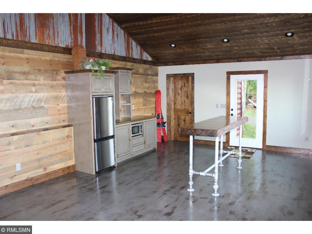 Lakeside beach house features custom built cabinetry with a refrigerator and microwave, vaulted ceiling done with resawn pine, resawn shiplap accent walls and reclaimed tin accents.