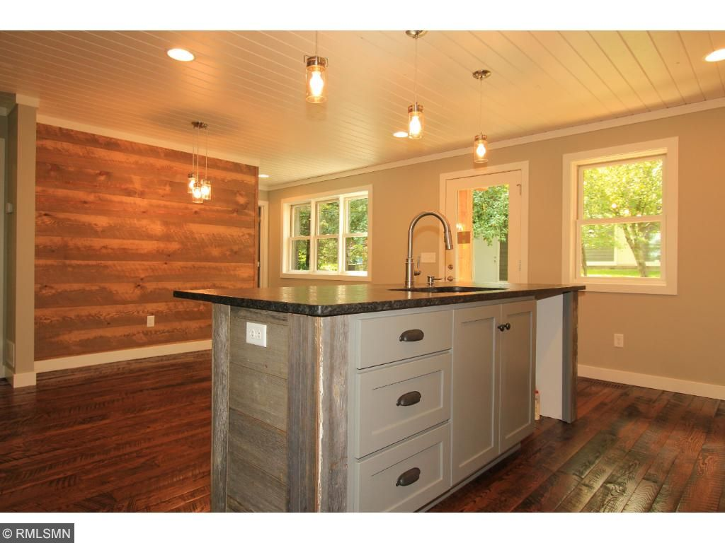 Kitchen also boasts a stunning reclaimed barn wood island that has a stone countertop and offers additional seating.