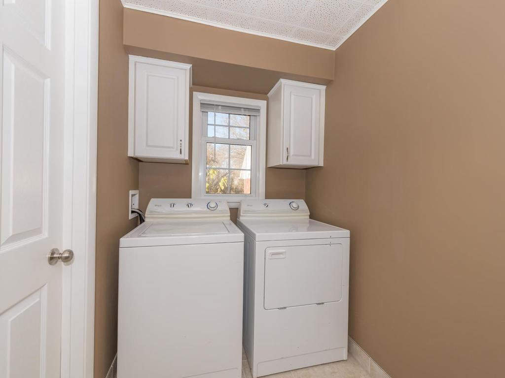 Laundry room with tile floors, cabinetry.  Door to the left is the mechanical room.