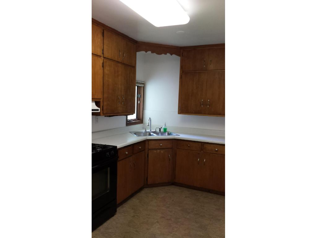 Kitchen features electric range, side-by-side refrigerator and kitchen window