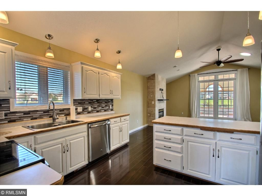 Wow! The kitchen has been recently updated with glass tile backsplash, freshly painted white cabinets, pendant lighting and stainless steel appliances.