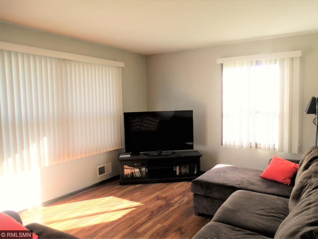 Spacious room is filled with natural light from the large east and south-facing windows.