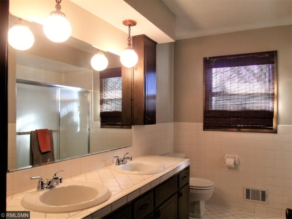 Roomy full bath on the main floor offers tub with tile surround, dual-sink vanity, and ample storage closet.