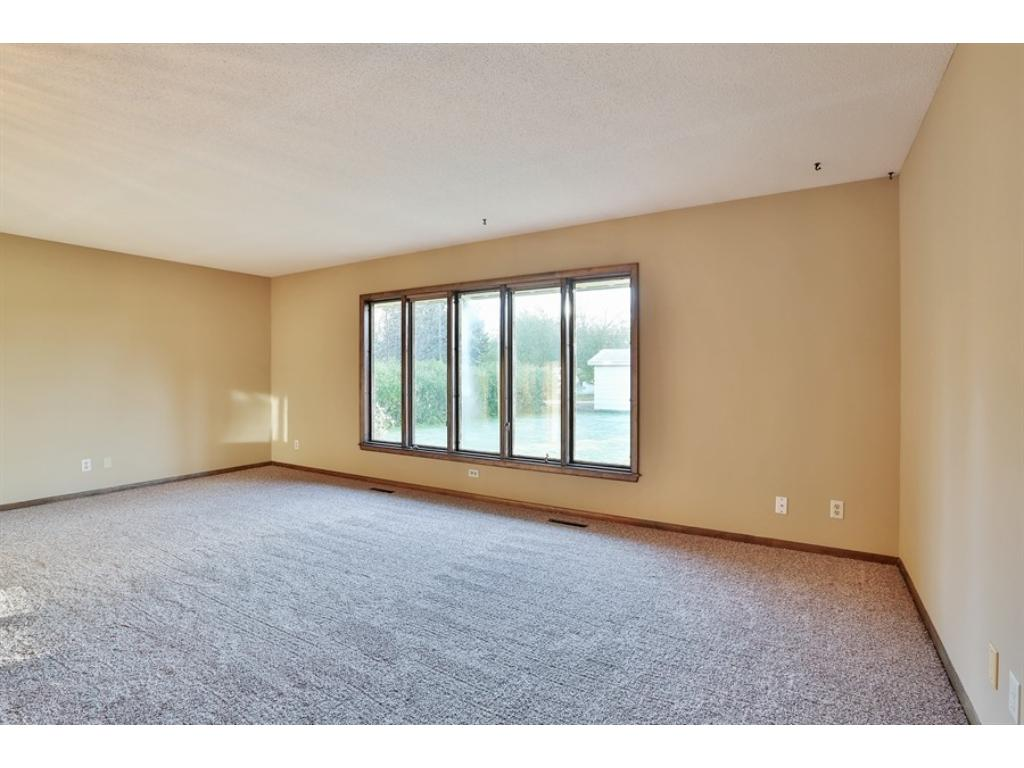 Large living room with large window overlooking large back yard. New carpet and paint.