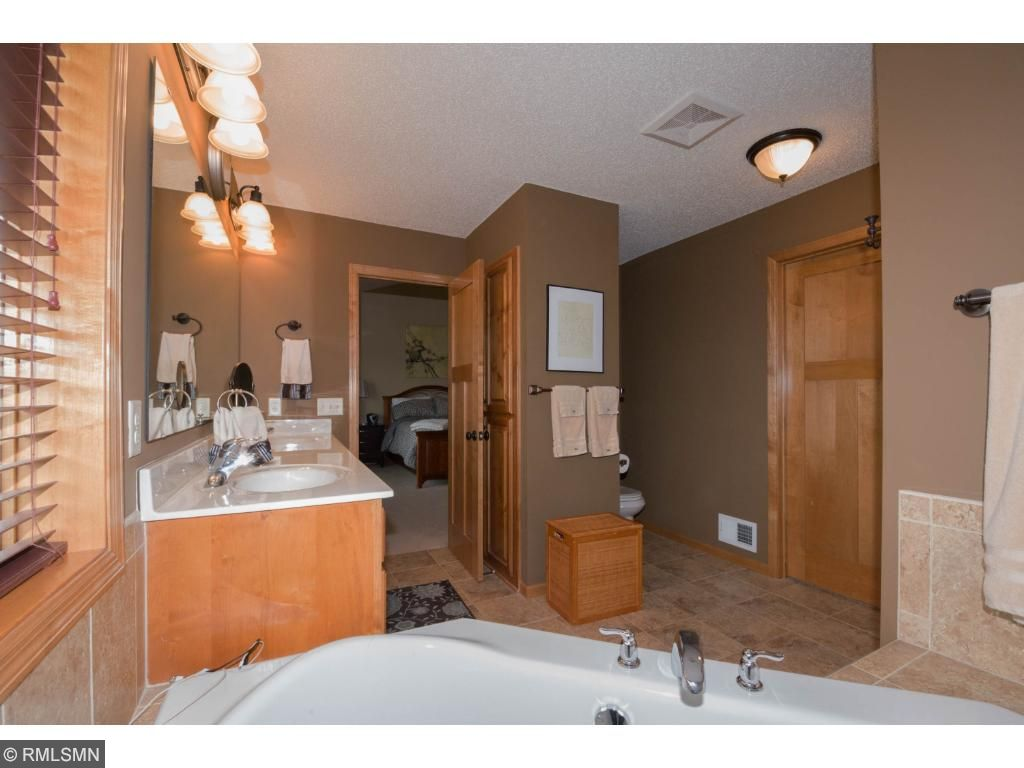 Large owners suite bath with double sinks, tub and shower.  Custom wood cabinetry and tiled floor.