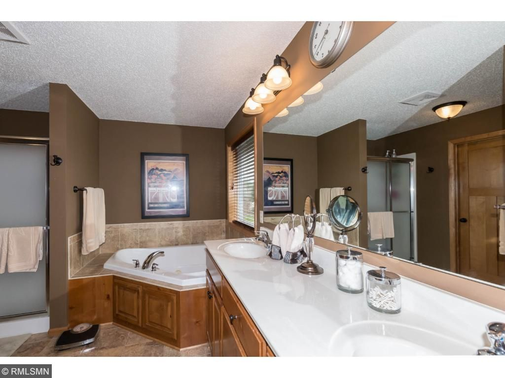 Double sinks in owners suite bath with mirrors.  Located conveniently by owners bedroom.  Neutral decor.  Walk-in closet off bath with plenty of room for storage.