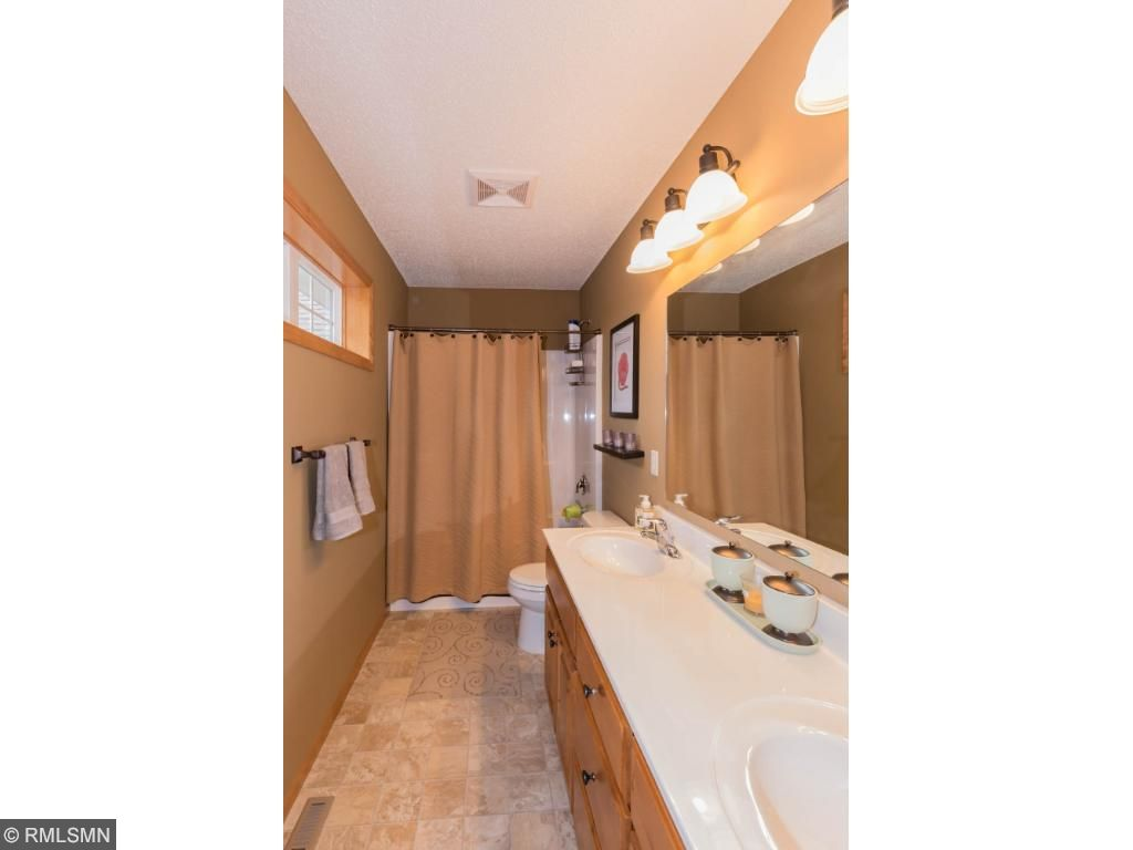 Hall bath with double sinks and lots of light from highly-positioned windows.  Tub with shower located near bedrooms and laundry.