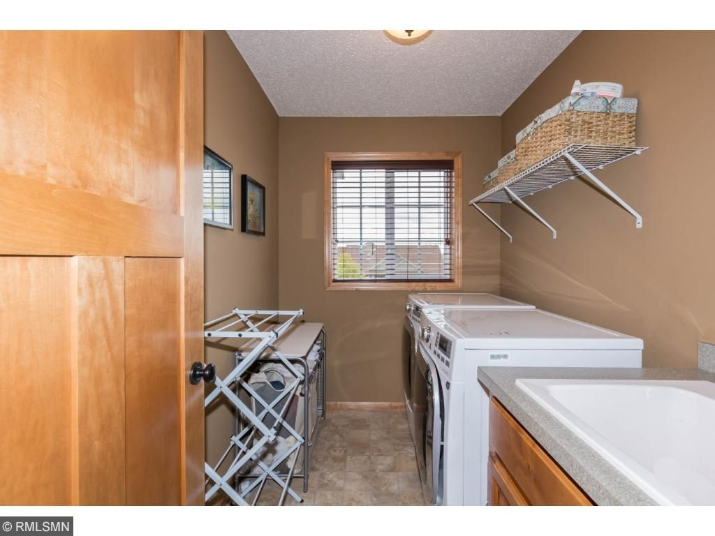 Second floor located located near bedrooms.  Washer and dryer cabineted laundry sink.  Front-facing window provides light and there's room for laundry activities.