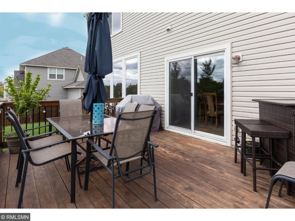 Stained wood deck with off dining area.  Steps above the patio for lots of outdoor living space.  Overlooks large flat yard edged with fencing and perimeter trees and shrubs.