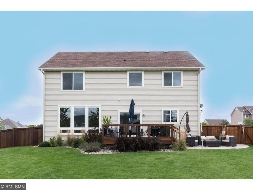 Exterior rear view of this Danita 2-story home.  Note the centrally-located deck with patio to the side.  Neutral siding and dark roof.  Fenced backyard at perimeter.  Gate around corner to 3-car garage.