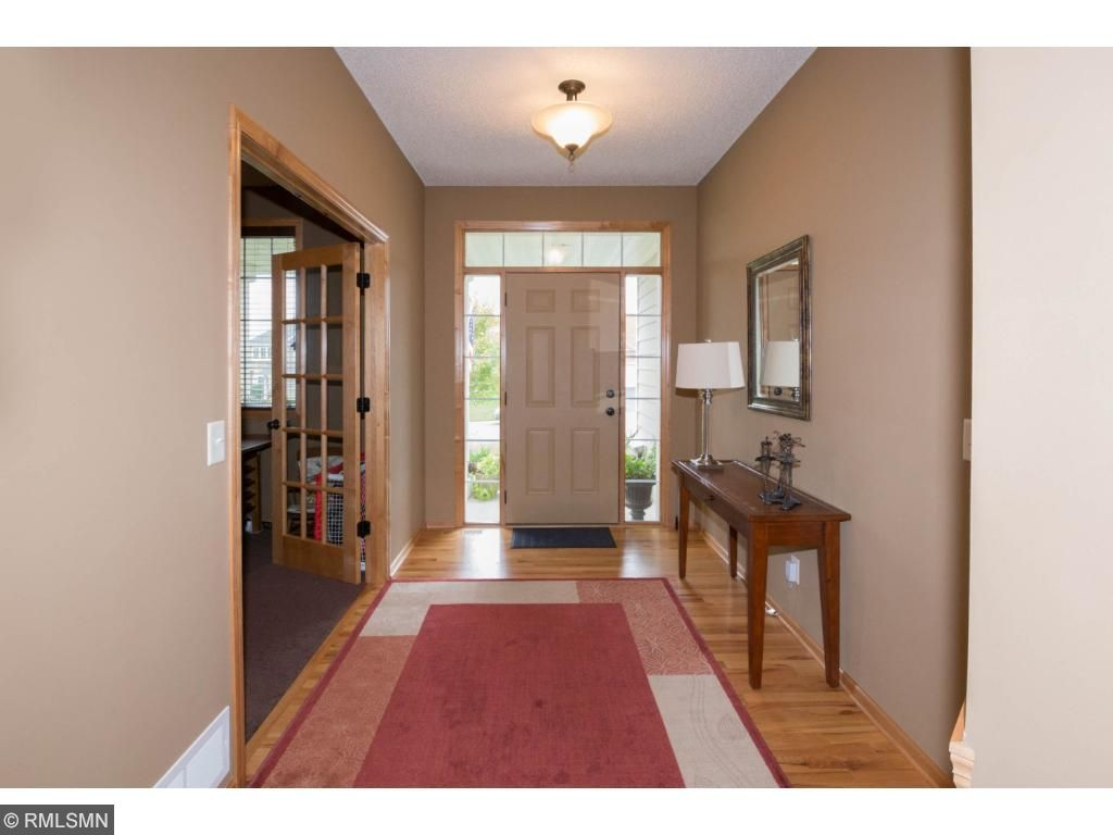 Covered front entry with side lights around 6-panel front door.  Wood floored entry foyer with closet opening to flex room and great room.  Well-lit foyer with bronze fixtures and natural woodwork.
