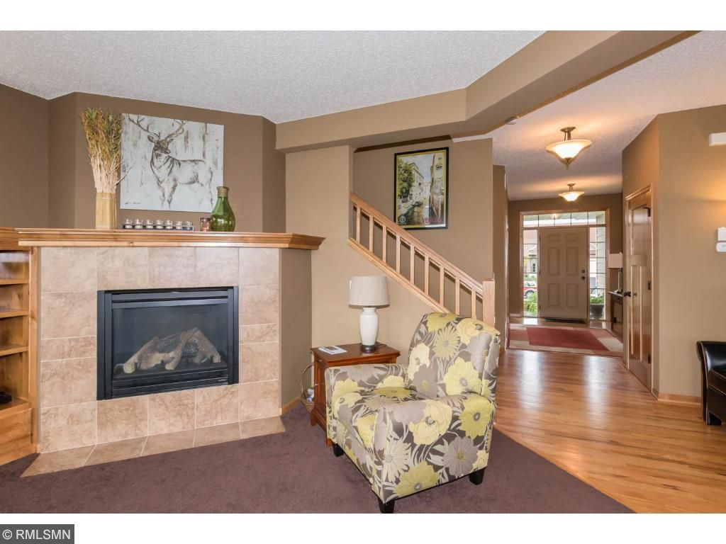Open floor plan leads from front foyer stairs up and down.  Great room with huge windows facing fenced backyard.  Great room has gas fireplace, custom wood built-ins.  Dark neutral carpeting and wood pillar divide great room from informal dining area