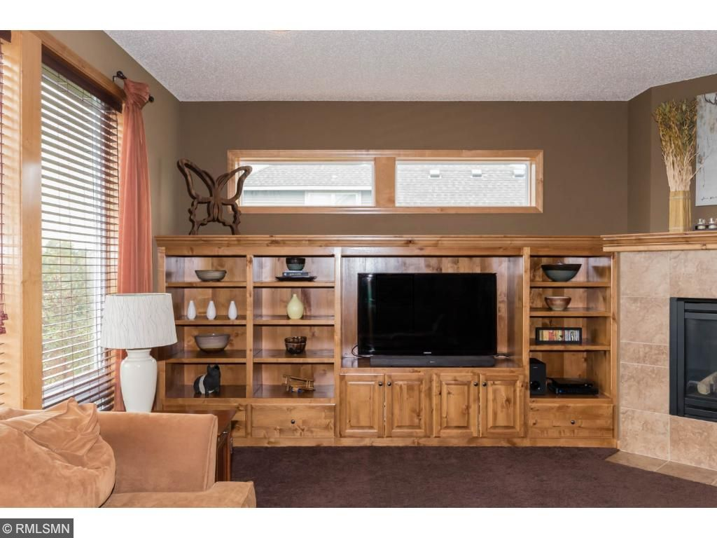 Custom wood built-ins in great room.  Floor to ceiling picture windows face beautifully landscaped backyard.  High-positioned windows bring in lots of light.  Carpeted room with space for relaxing.  Gas fireplace in corner adds to room ambience.