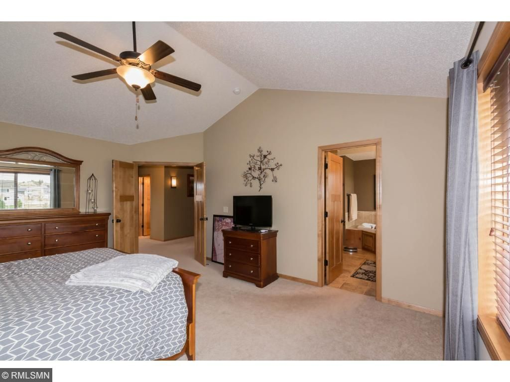 Owners suite has a large bedroom with cathedral ceiling with fan.  Lots of windows facing backyard.  Connected to large bath with shower and tub.  Huge walk-in closet.  Neutral decor.