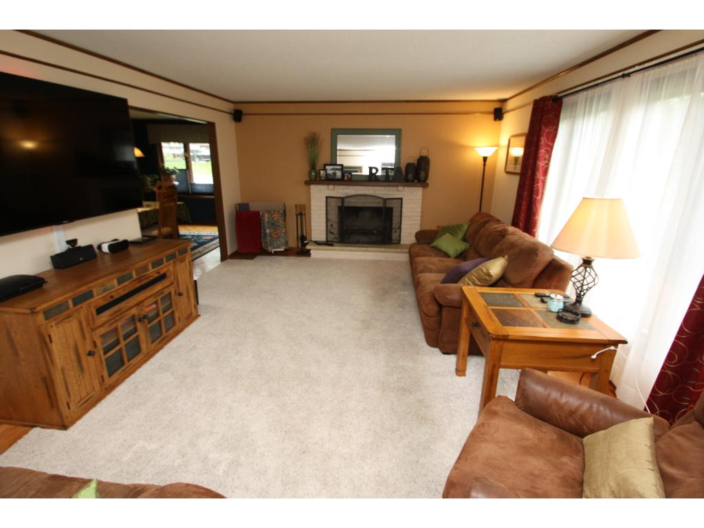 Large living room with fireplace...lots of windows too.