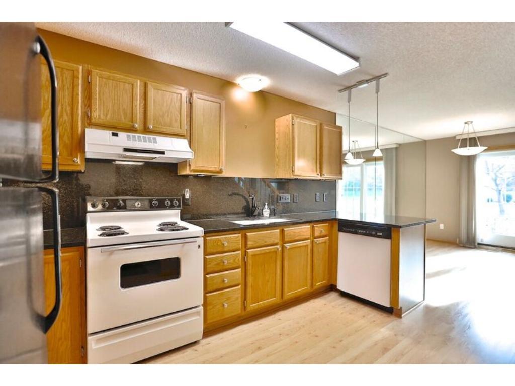 Kitchen with hardwood like floors opens to patio