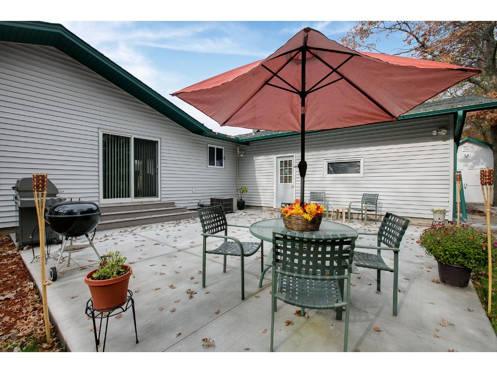 Large patio offers additional entertaining space and a welcoming view of the large lot and mature trees.