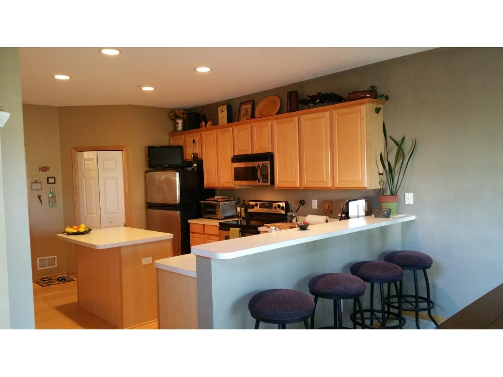 Large kitchen with SS appliances, large island provides lots of extra prep space and breakfast bar - great for entertaining, maple floors and cabinets, large pantry, high ceilings, and access to 1/2 bath and garage