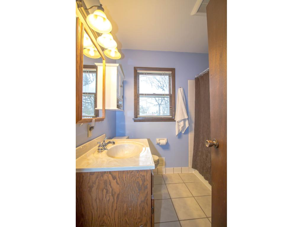 The full bath offers a tile shower/tub surround, and a window for natural light.