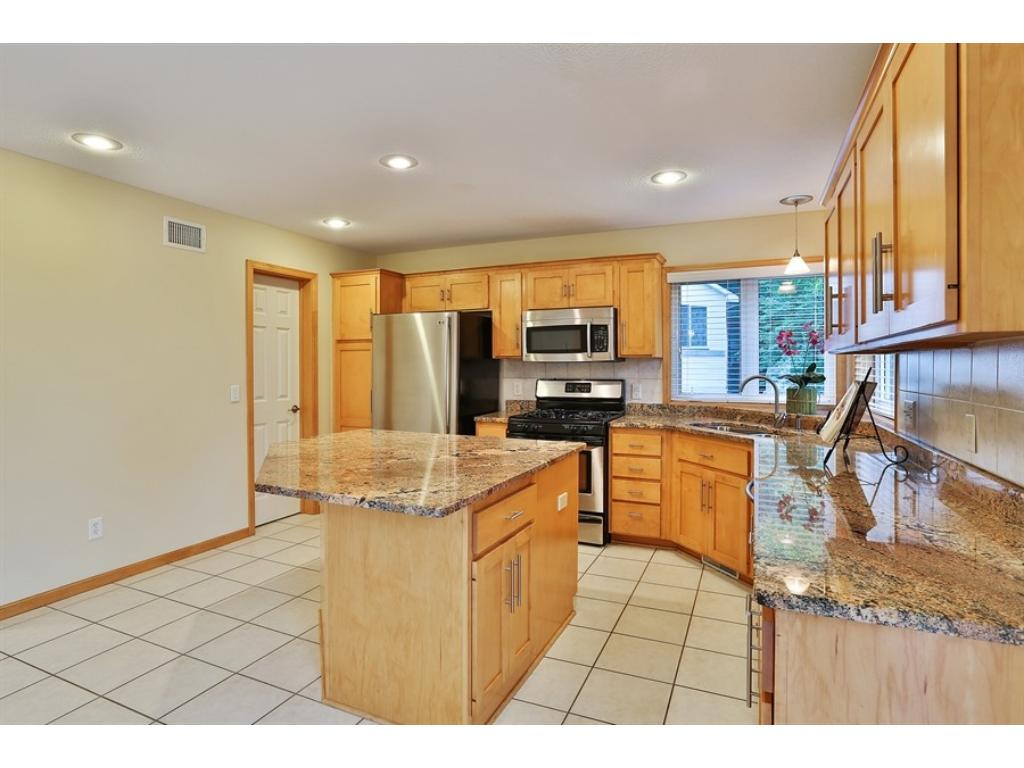 Big center island Kitchen with GORGEOUS GRANITE COUNTERTOPS, walk-in pantry, maple cabinets, tile floors and stainless appliances.