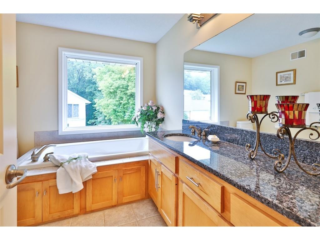 Beautiful Master Bath with a soaking tub, granite countertops and a tile floor.