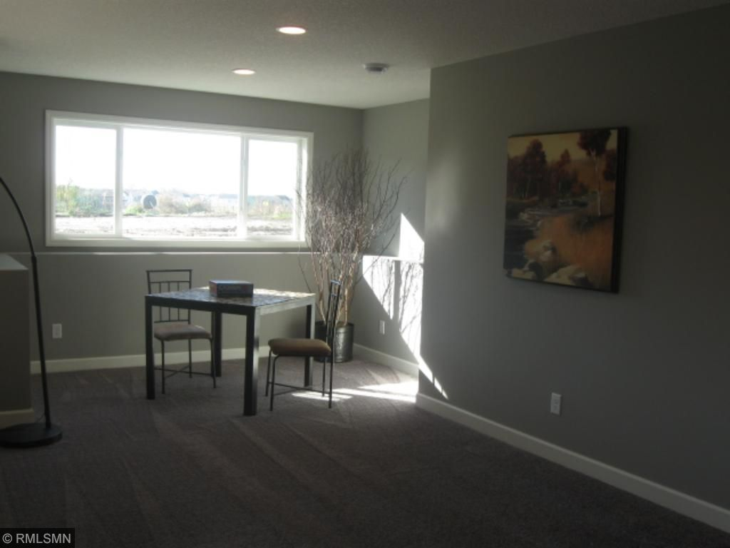 neat area for a game table, working a puzzle, exercise area with an abundance of natural light.  The lower level also includes a bedroom.