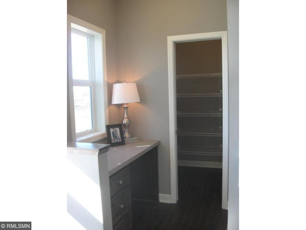 Walk-in pantry includes wire shelves for kitchen appliances and food.  You'll notice the nice work station desk that overlooks an open back yard and a pond view