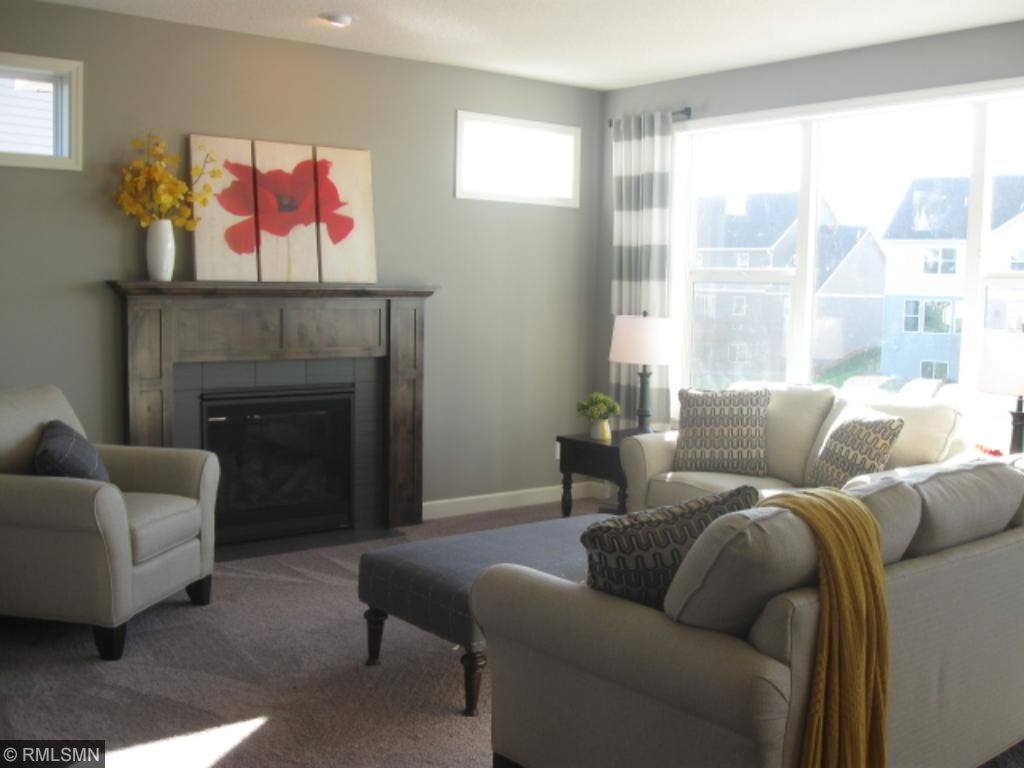Lovely great room with tile surround fireplace and piano windows.  Lots of natural light