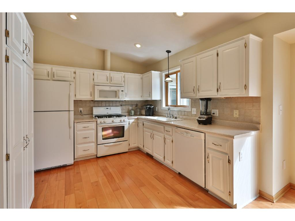 The kitchen features hardwood floors, vaulted ceilings, and is open to the formal and informal dining spaces.