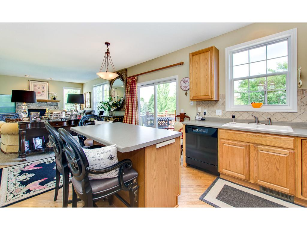 The kitchen boasts a center island, tile back splash, hardwood floors & pantry!
