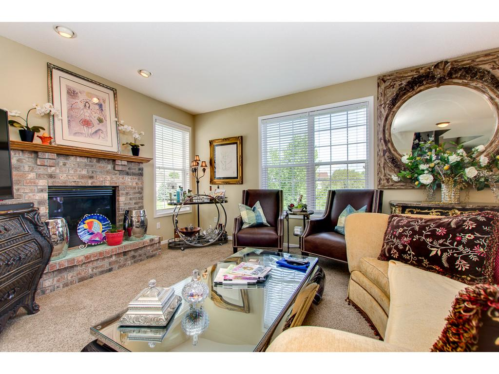 The main floor living room is complete with gas fireplace with brick surround...