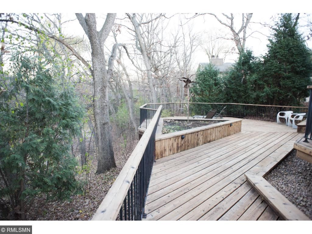 Deck is built in the back and overlooks the hillside of the backyard that goes down to a pond area.